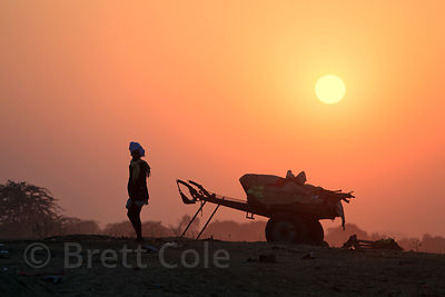 People walk near a cart in the desert at sunset, Pushkar, Rajasthan, India.