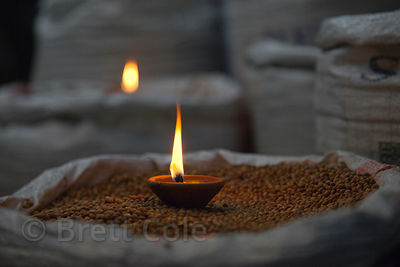 Candle placed in a bag of grain during Diwali festival, Jaipur, Rajasthan, India