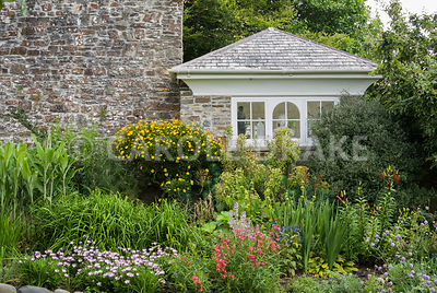 The music room with mixed border in front including euphorbia, phlomis and lilies. Clovelly Court, Bideford, Devon, UK
