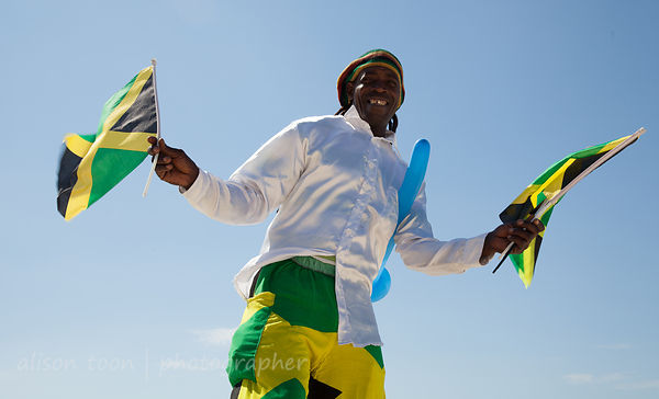 JANUARY 2013: MONTEGO BAY, JAMAICA: Stilt man with flags