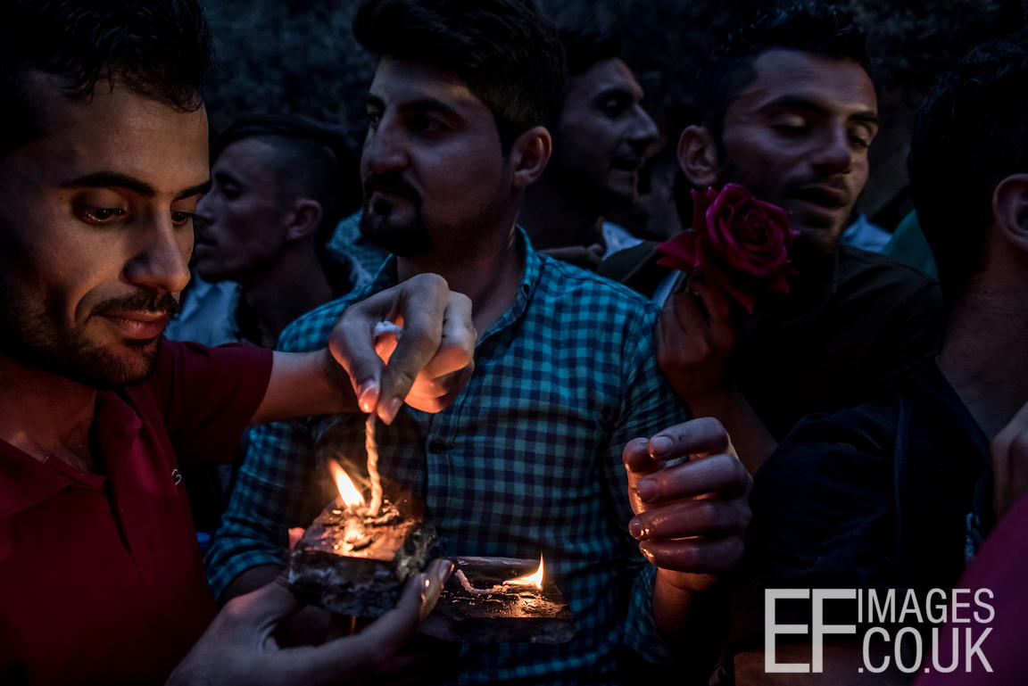 Young men with oil lamps and a red rose celebrating Yazidi New Year, or Sere Sal