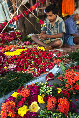 Workers string flowers at the Howrah Flower Market, Kolkata, India. It's the largest flower market in Asia.
