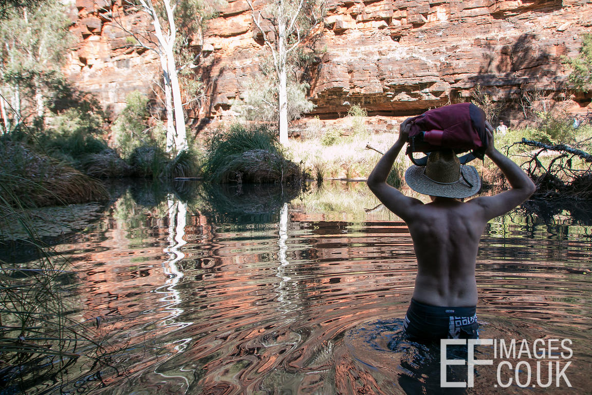 Man Wading Through A Creek With A Pack On His Head
