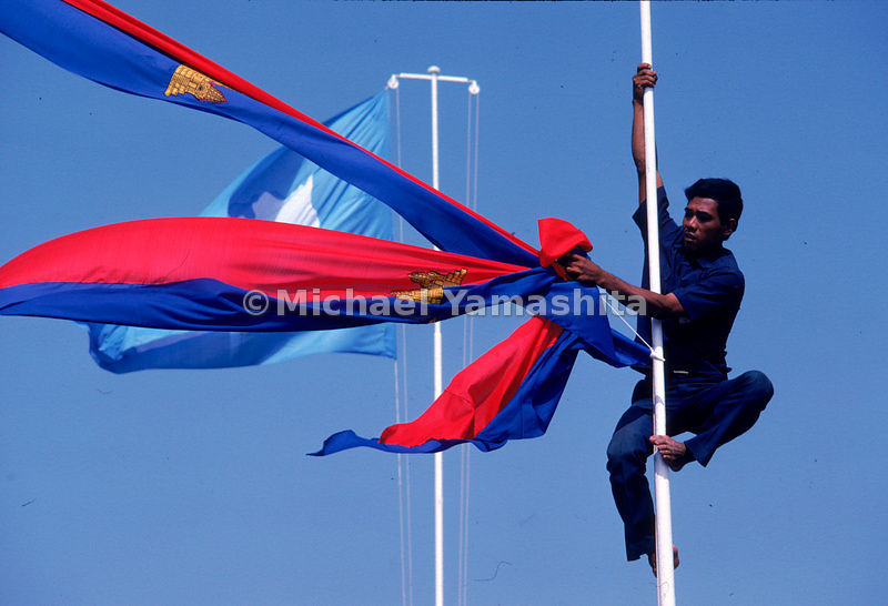 Cambodian flags, with the image of Angkor Wat emblazoned on them, are raised in tribute to mark the return of Prince Sihanouk.