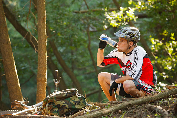 solo mountain bike riding man drinking from camelbak water bottle