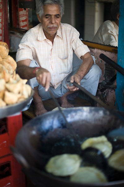India - Delhi - A man fries bread in a large frying pan at a stall in Chadni Chowk