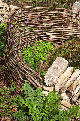 The 'Coppice' woodland enclosure garden - a sustainable garden at RHS Hampton Court Flower Show. Designers: Matthew Allan and...