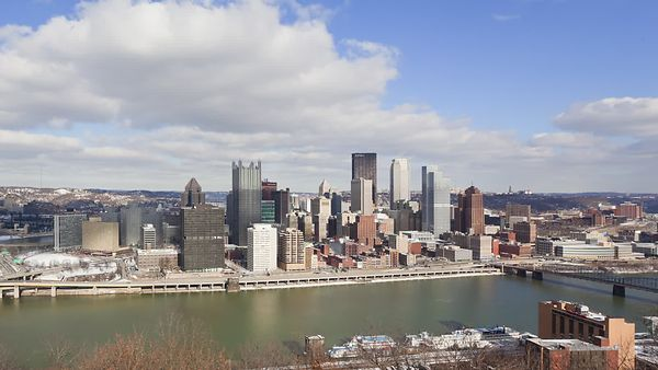 Medium Shot: Monongahela River Besetting A Sunny Pittsburg Skyline