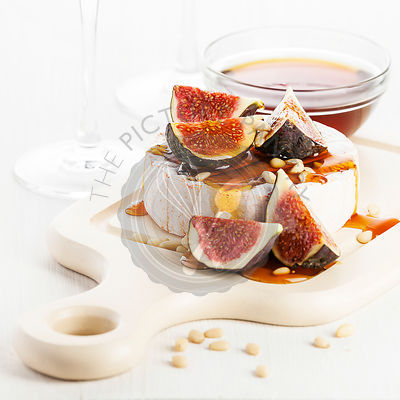 Camembert cheese, figs and honey on light background