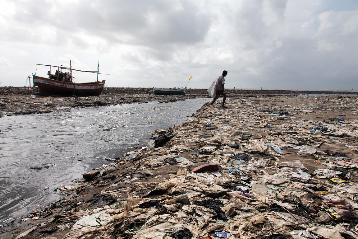 A solid mat of plastic garbage lines the beach along a freshwater inflow to the Arabian Sea along Juhu Beach in Mumbai, India.