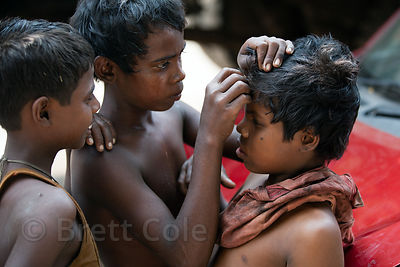 Two boys use a razor blade to trim the hair of another boy, on Strand Road, Kolkata, India.