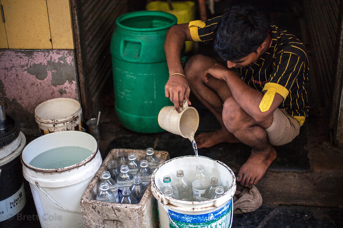 A man fills up bottles of water with unfiltered tap water to sell, in Dharavi, by most account the most crowded square mile o...