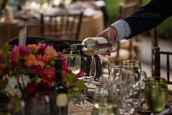 Server pours glasses of white wine at a restaurant