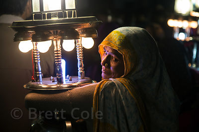 A woman carries a lantern during a marriage procession, Badi Basti, Pushkar, Rajasthan, India. Low caste adults are paid just...
