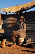 Nama man in front of corrugated iron shack. Nama people resettled in Riemvasmaak after the apartheid era, Riemvasmaak, South ...