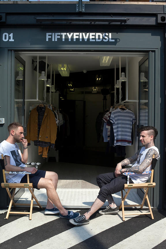 UK - London - A shop assistant with many tattoos sits outside his shop at the Boxpark - a so-called 'pop up mall' comprising ...