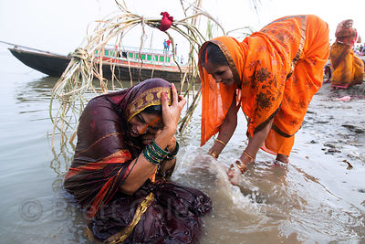 Women splash each other with water during Chhath Puja, Varanasi, India. Chhath Puja is a devotion to the Sun God Surya in whi...