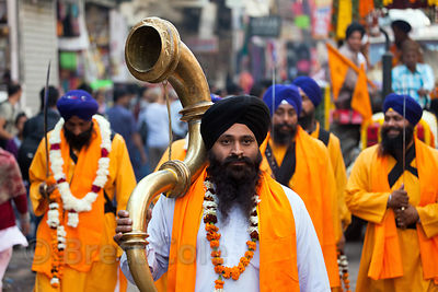 A Sikh man hold a large horn in a parade in the Paharganj neighborhood of Delhi, India.