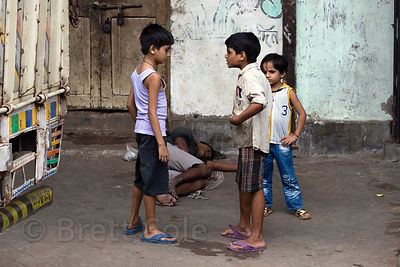 Children argue as a man lies passed out and drunk on the sidewalk behind them., Strand Rd., Jorabagan, Kolkata, India