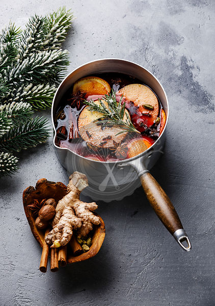Mulled wine hot drink with citrus, apple and spices in aluminum pan