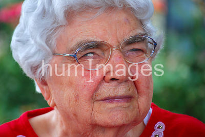 Silver haired woman with glasses (red shirt)