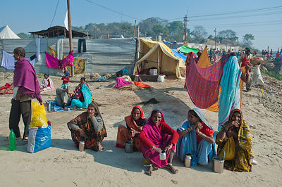 A common scene at the Kumbh Mela. These women rest in front of their makeshift houses.