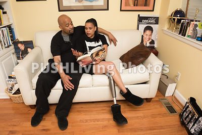 Woman with aprosthetic leg sitting on a couch with her partner reading a book