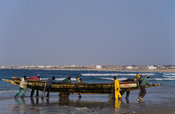 a fishing pirogue is being rolled onto the beach, Dakar, Senegal