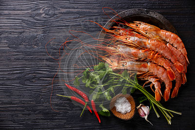 Raw fresh Prawns on metal plate on black burned wooden background copy space