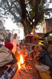 Men huddle around a fire to stay warm on a winter morning, Varanasi, India.