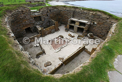 Interior of House 1, Skara Brae neolithic farming village, showing central hearth, box bed, dresser and grinding stone