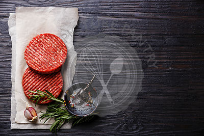 Raw Ground beef meat Burger steak cutlets and seasonings on black burned wooden background copy space