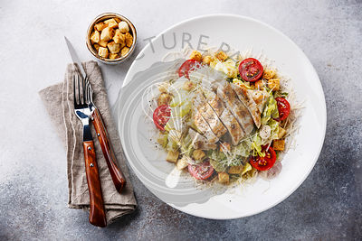 Caesar salad with chicken breast and croutons on gray background