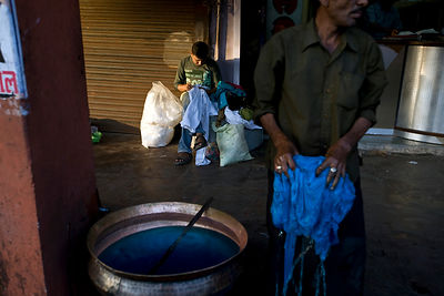 India - Jaipur - A man dyes cloth blue while a tailor mends clothes behind him