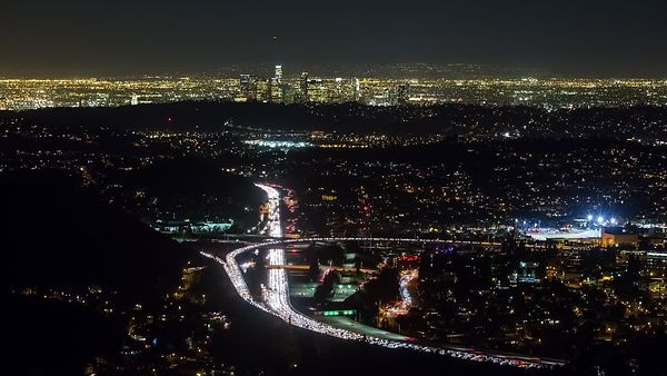 Bird's Eye: Arterial Blockage - Traffic Jam In Front Of L.A. Skyline At Night