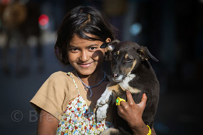 A girl with her adopted street dog puppy, Pushkar, Rajasthan, India
