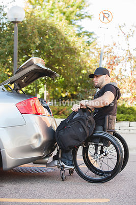 Young male college student in a wheelchair getting into his car