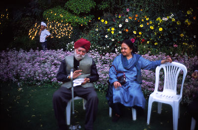 India - Delhi - A couple talk at a society garden party