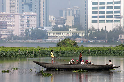Fishermen ply the waters of the East Kolkata Wetlands, Kolkata, India, with the backdrop of Salt Lake City reflecting in the ...