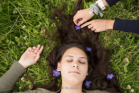 A girl lying on the grass with flowers.