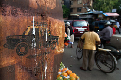 Weathered and rusted sign with a graphic of an ambassador taxi, Bandra East, Mumbai, India.