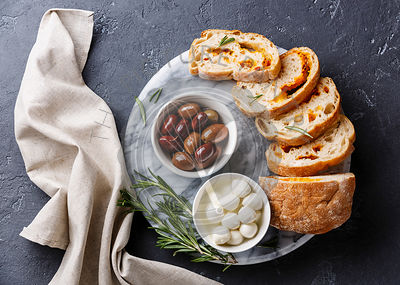 Olives, mini Mozzarella cheese and sliced Ciabatta bread with cheese on dark background