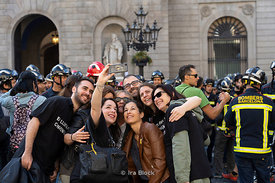 Tourists taking selfies at Plaça Sant Jaume in Barcelona, Spain.