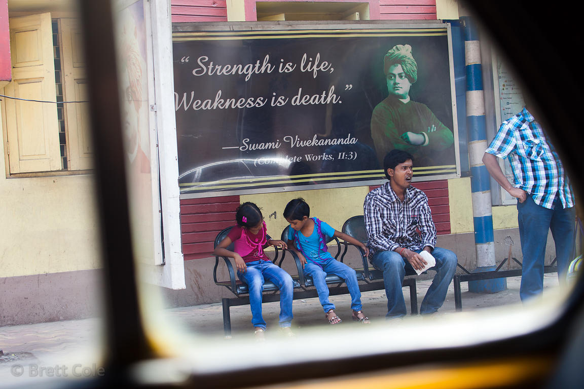 "Billboard reading ""Strength is life, Weakness is death"" at a bus stop in Sovabazar, Kolkata, India."