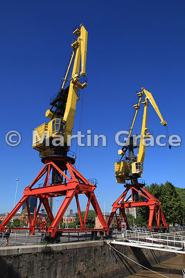 Puerto Madero docklands regeneration in Buenos Aires, Argentina, showing restored cranes against the clear blue sky