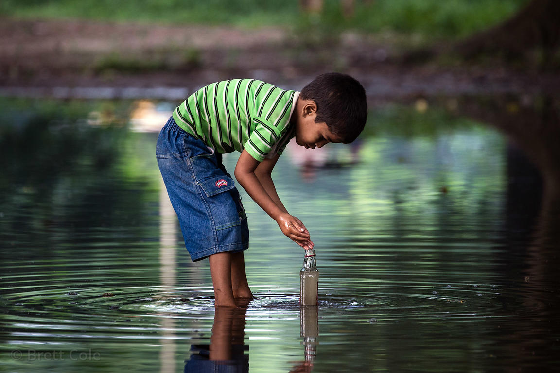 A boy collects unsafe drinking water from a pond of rainwater, Maidan, Kolkata, India