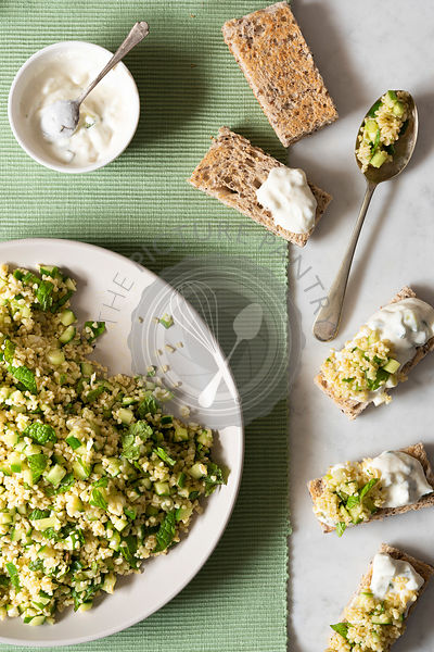 Preaparation of cucumber tabouli salad and tzatziki dressing on toast fingers.