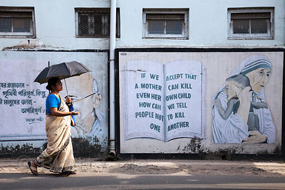 A woman with an umbrella walks past a mural with a quote by Mother Teresa.