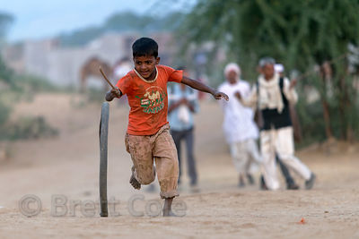 A boy rolls a hoop in the Thar Desert in Pushkar, Rajasthan, India
