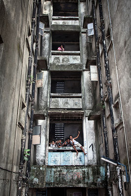 Residents pose in a weathered high-rise apartment in the Dharavi slum, Mumbai, India.